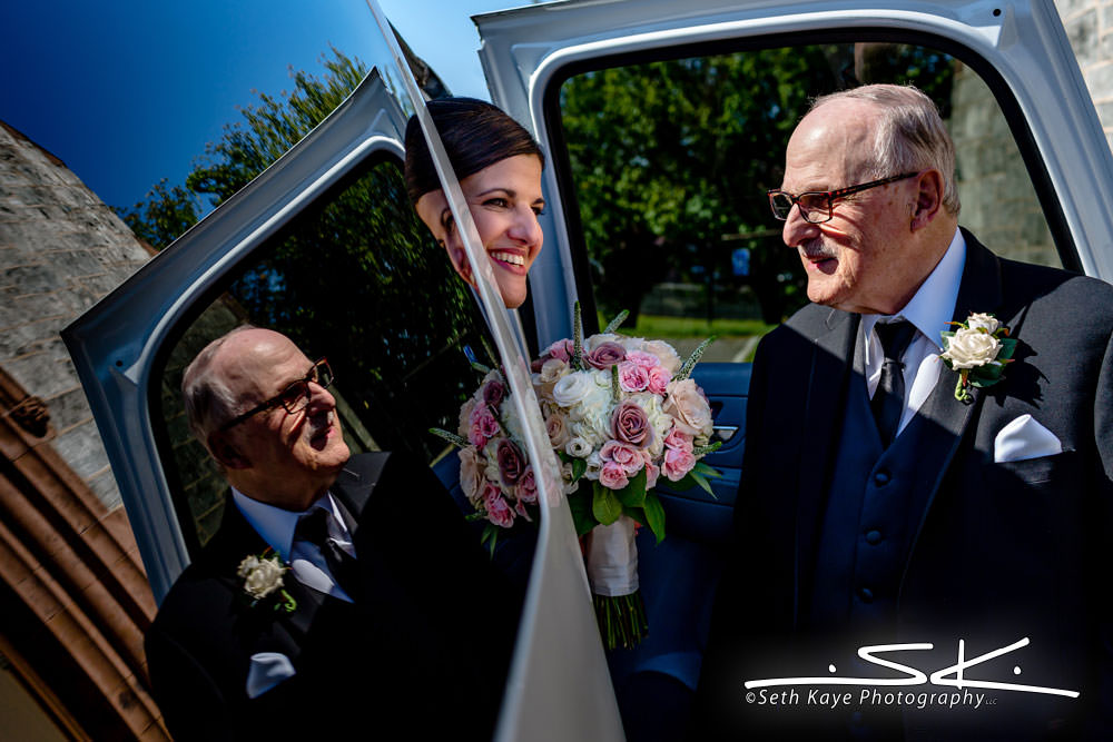 father helping bride out of the limo